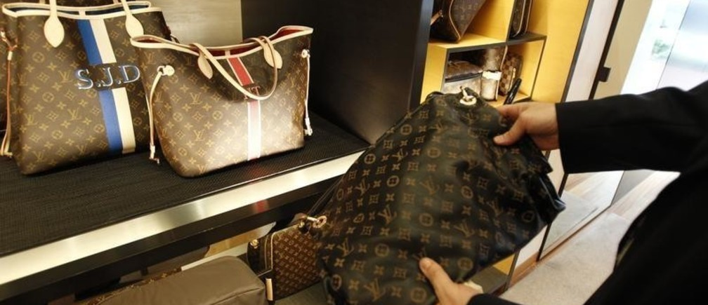 A fake LVMH handbag (R) purchased and shipped from a China -ased online website is pictured next to products on display at a Louis Vuitton store in Chevy Chase, Maryland, October 5, 2010. The Organization for Economic Cooperation and Development estimates the amount of counterfeit goods and pirated copyrights in world trade grew from about $100 billion in 2001 to about $250 billion in 2007, the last year for which they have made an estimate. In the 2009 budget year, U.S. Customs agents and other officials made 14,481 seizures valued at $260.7 million dollars. Picture taken October 5, 2010.   To match Special Report CHINA-PIRACY/    REUTERS/Hyungwon Kang (UNITED STATES - Tags: CRIME LAW BUSINESS) - GM1E6AQ1EVH01