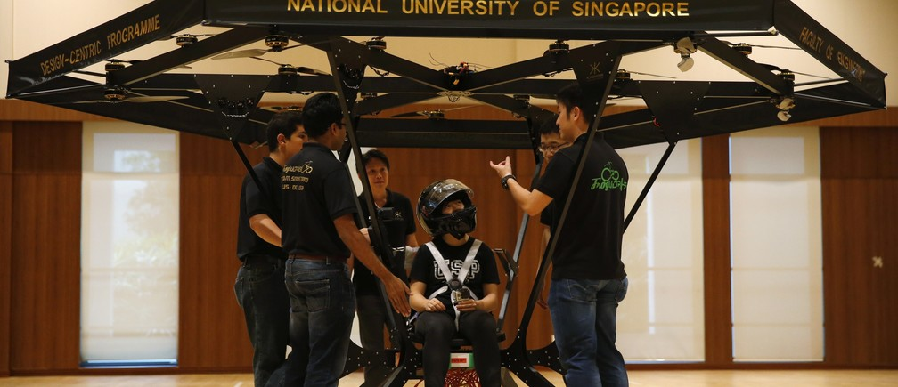Zheng Xiaowen sits in the Snowstorm, a personal flying machine built by a group of engineering students of the National University of Singapore (NUS), as team members discuss in NUS gymnasium in Singapore December 10, 2015.