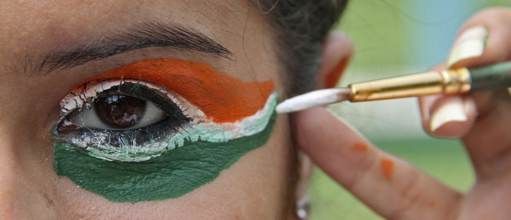 A college girl gets her eye painted in tri-colours of India's national flag on the eve of the country's Independence Day celebrations in the northern Indian city of Chandigarh August 14, 2012. REUTERS/Ajay Verma (INDIA - Tags: SOCIETY ANNIVERSARY) - GM2E88E192W01