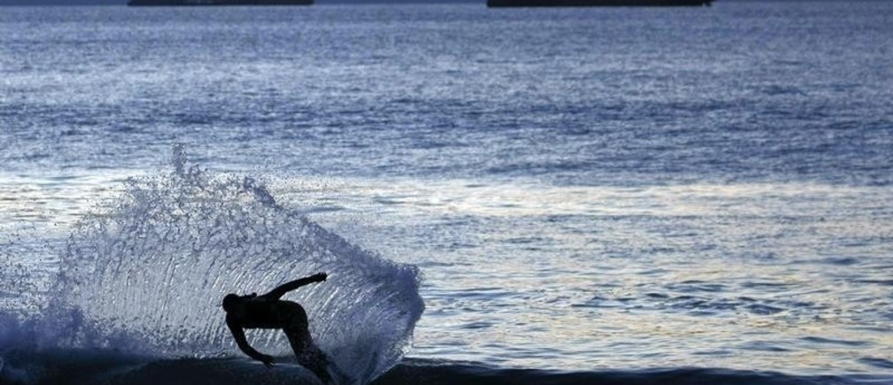 A surfer rides a wave during sunset  in Vina del Mar city, about 75 miles (121 Km) northwest of Santiago, March 20, 2010. People slowly return the normal life in the coastal border after suffering an earthquake and tsunamis in much of southern Chile on February 27, 2010. REUTERS/Eliseo Fernandez (CHILE - Tags: SOCIETY IMAGES OF THE DAY) - RTR2BVIJ