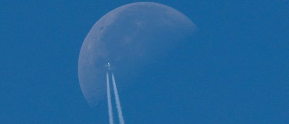 A passenger plane flies in the sky as the Moon is seen in Berlin, Germany, August 23, 2019.     REUTERS/Fabrizio Bensch - RC1EAD948770