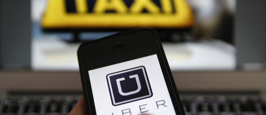 An illustration picture shows the logo of car-sharing service app Uber on a smartphone next to the picture of an official German taxi sign in Frankfurt, September 15, 2014. A Frankfurt high court will hold a hearing on a recent lawsuit brought against Uberpop by Taxi Deutschland on Tuesday. San Francisco-based Uber, which allows users to summon taxi-like services on their smartphones, offers two main services, Uber, its classic low-cost, limousine pick-up service, and Uberpop, a newer ride-sharing service, which connects private drivers to passengers - an established practice in Germany that nonetheless operates in a legal grey area of rules governing commercial transportation. The company has faced regulatory scrutiny and court injunctions from its early days, even as it has expanded rapidly into roughly 150 cities around the world.