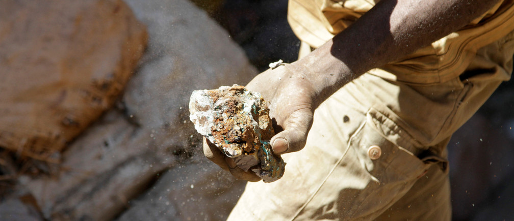An miner carries raw ore at a former industrial copper-cobalt mine in the Democratic Republic of the Congo