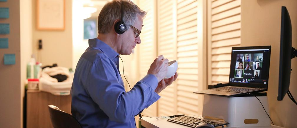 Doug Hassebroek desayuna mientras está en una videoconferencia trabajando desde su casa durante el brote de la enfermedad coronavirus (COVID-19) en Brooklyn, Nueva York, EE.UU., 24 de abril de 2020.