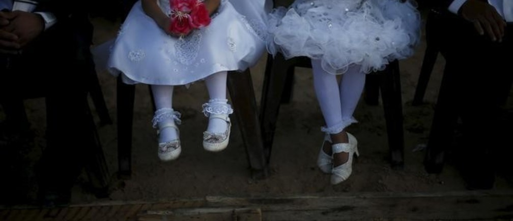 Girls accompany grooms as they sit separate from the brides during a mass wedding for 150 couples in Beit Lahiya town in the northern Gaza Strip July 20, 2015. The wedding was funded by al-Basheer Society for Relief and Development. REUTERS/Suhaib Salem