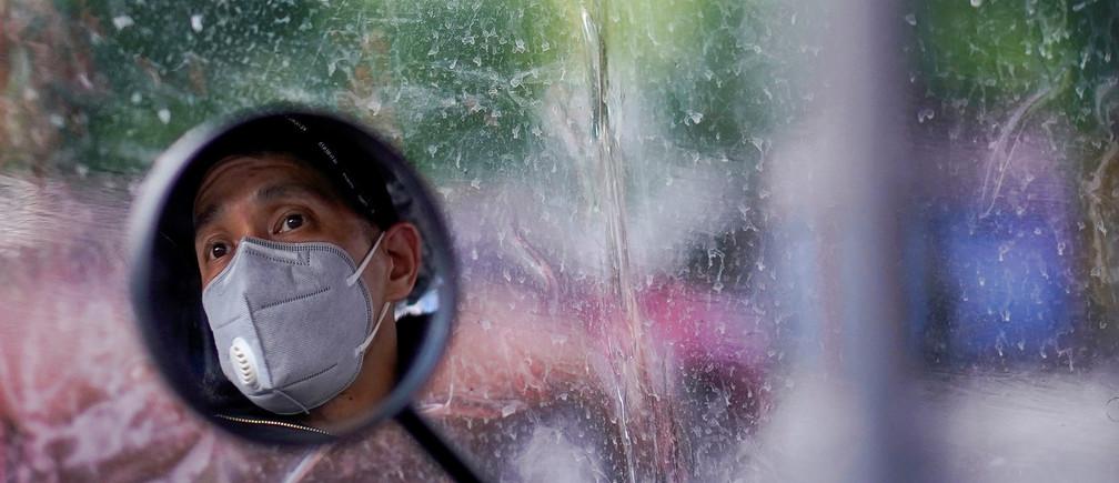 Se ve a un hombre con una máscara facial, reflejada en el espejo retrovisor de su bicicleta eléctrica, en una calle después de que se levantara el bloqueo en Wuhan, capital de la provincia de Hubei y epicentro del brote de la nueva enfermedad coronavirus (COVID-19) en China, el 14 de abril de 2020.