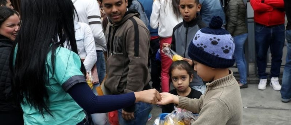A Venezuelan migrant child sells food outside their embassy while others wait to register for a flight to return to their country, in Lima, Peru September 5, 2018.