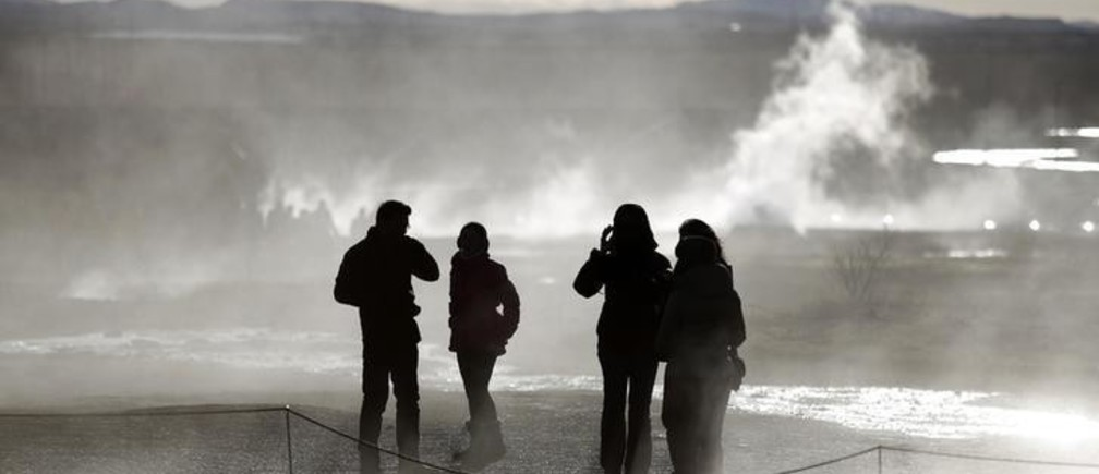People walk in the mist of sulphuric fumes at the site of the Great Geysir in southwestern Iceland February 15, 2013.          REUTERS/Stoyan Nenov (ICELAND - Tags: TRAVEL)