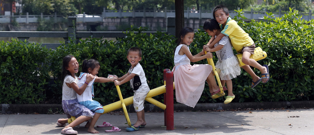 Yang Hongnian and Le Huimin's six children play on a see-saw outside their home in Jinhua, Zhejiang province, August 7, 2014