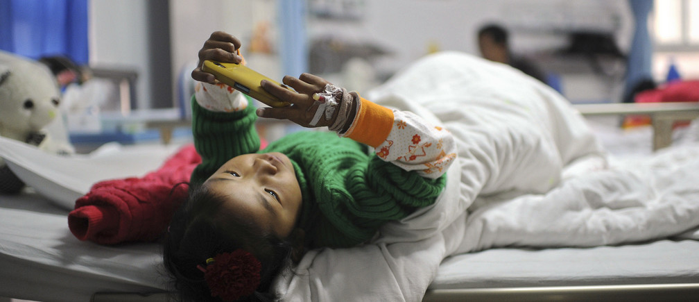 A seven-year-old ethnic Tibetan girl diagnosed with congenital heart disease plays with a mobile phone as she lies on bed before having her surgery at a hospital in Hefei, capital of eastern China's Anhui province, December 22, 2012.