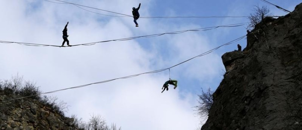 Participants balance on lines during a highline event near the town of Beroun, Czech Republic March 24, 2018.