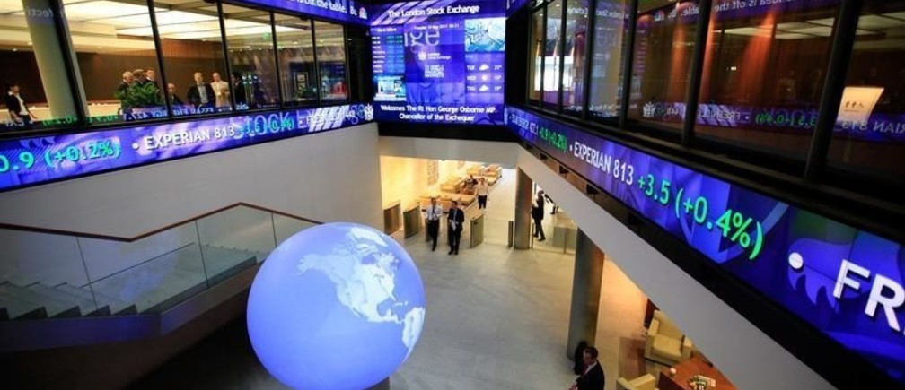 Financial data and news headlines stream accross ticker screens around the atrium of the London Stock Exchange after Britain's Chancellor of the Exchequer George Osborne inaugurated the ceremonial market opening in the City of London, May 10, 2011.  REUTERS/Andrew Winning (BRITAIN - Tags: POLITICS BUSINESS) - RTR2M7G0