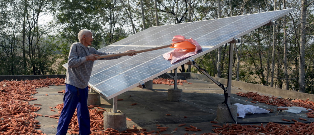 A man cleans a solar panel installed on his rooftop for free by the government in China