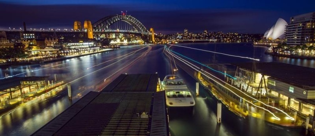 Streaks of light from arriving ferries illuminate wharves at Sydney's Circular Quay terminal in this seven-minute-long time exposure at dusk, July 16, 2015. Sydney's ferry system has been its lifeblood since the mid 1800s, transporting more than 15 million individual passenger journeys each year, according to the Bureau of Transport Statistics. From fast-food employees to finance industry executives, more than 40,000 trips are taken every day. Picture taken July 16, 2015. REUTERS/Jason Reed      TPX IMAGES OF THE DAY      - GF20000078043