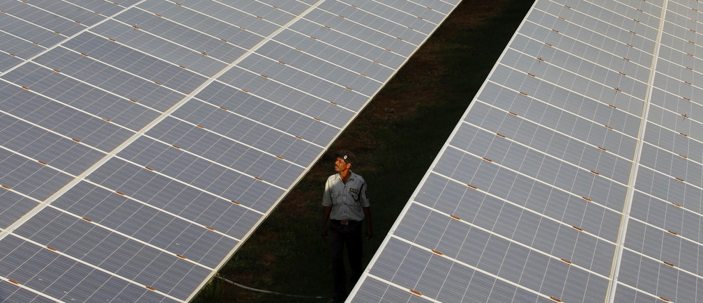 A private security guard walks between rows of photovoltaic solar panels inside a solar power plant at Raisan village near Gandhinagar, in the western Indian state of Gujarat, February 11, 2014. India said on Tuesday it was investigating U.S. policies supporting solar panel makers, the latest move in an escalating row over renewable energy that has worsened already strained ties between the two countries. REUTERS/Amit Dave (INDIA - Tags: POLITICS BUSINESS ENERGY TPX IMAGES OF THE DAY) - GM1EA2B1RUN01