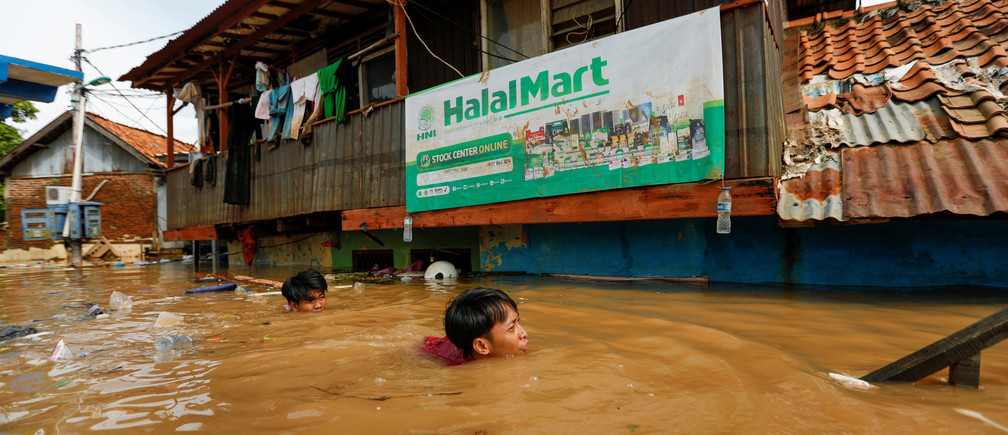Men swim as they collect items from their houses, flooded after heavy rains in Jakarta, Indonesia, January 2, 2020.