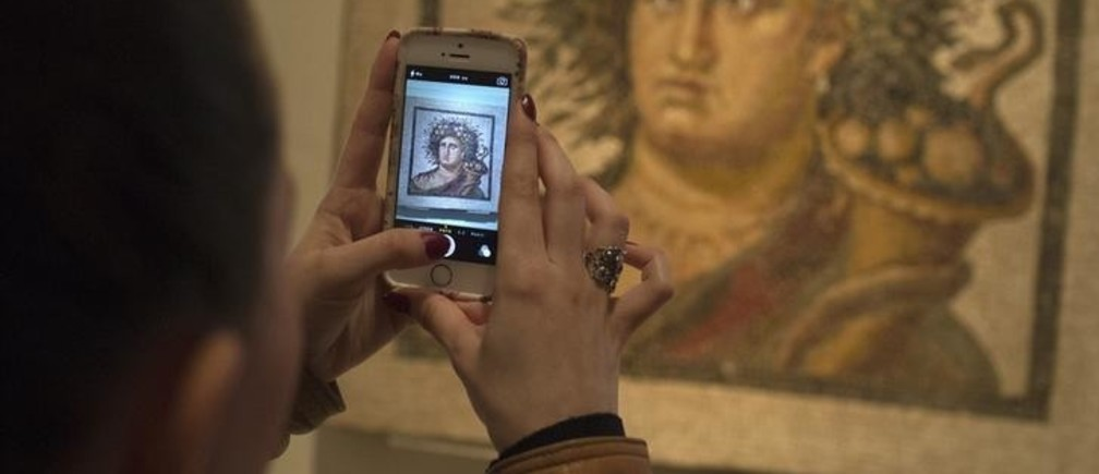 "A woman takes a picture with her cell phone of ""Genius of the Year"", a mosaic dating from the late 2nd century, at the National Archaeological Museum in Madrid March 27, 2014. REUTERS/Juan Medina (SPAIN - Tags: SOCIETY)"