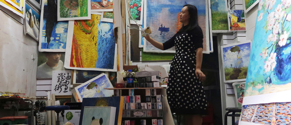 Ma Chunyan, 32, works on reproducing a masterpiece from an image of the original displayed on her mobile phone at her studio in Dafen Oil Painting Village in Shenzhen, Guangdong province, China December 5, 2018. Picture taken December 5, 2018. REUTERS/Thomas Suen - RC1DA087F7D0