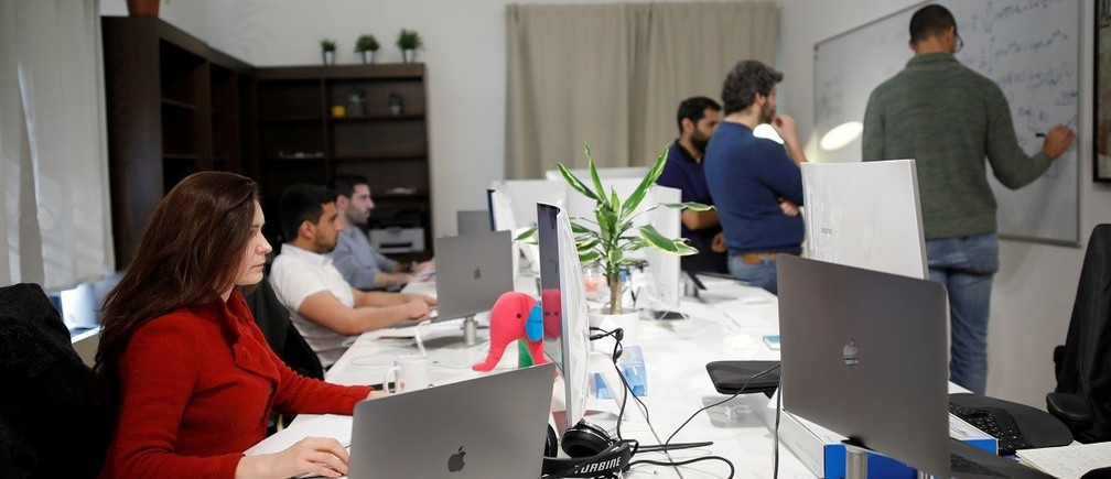 Employees of the D-ID startup company work at the company's office in Tel Aviv, Israel February 7, 2018. Picture taken February 7, 2018. REUTERS/Amir Cohen - RC1CD7849780