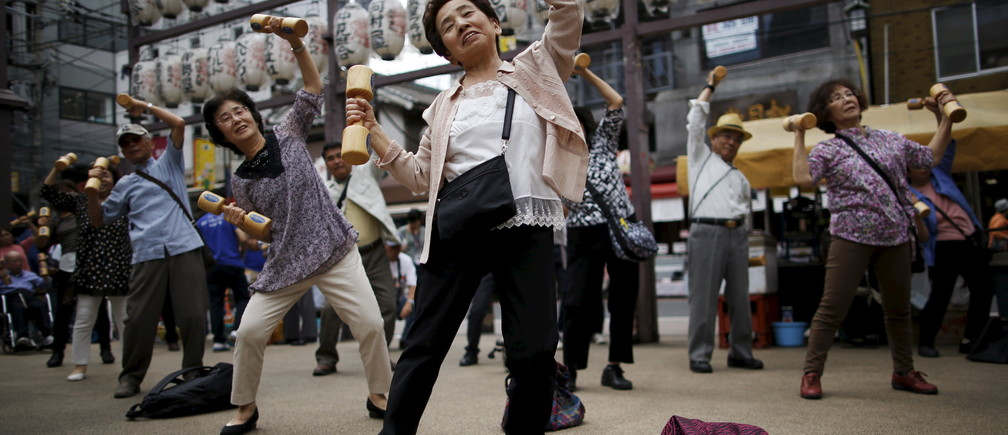 "Elderly and middle-age people exercise with wooden dumbbells during a health promotion event to mark Japan's ""Respect for the Aged Day"" at a temple in Tokyo's Sugamo district, an area popular among the Japanese elderly, September 21, 2015. REUTERS/Issei Kato      TPX IMAGES OF THE DAY      - RTS235V"
