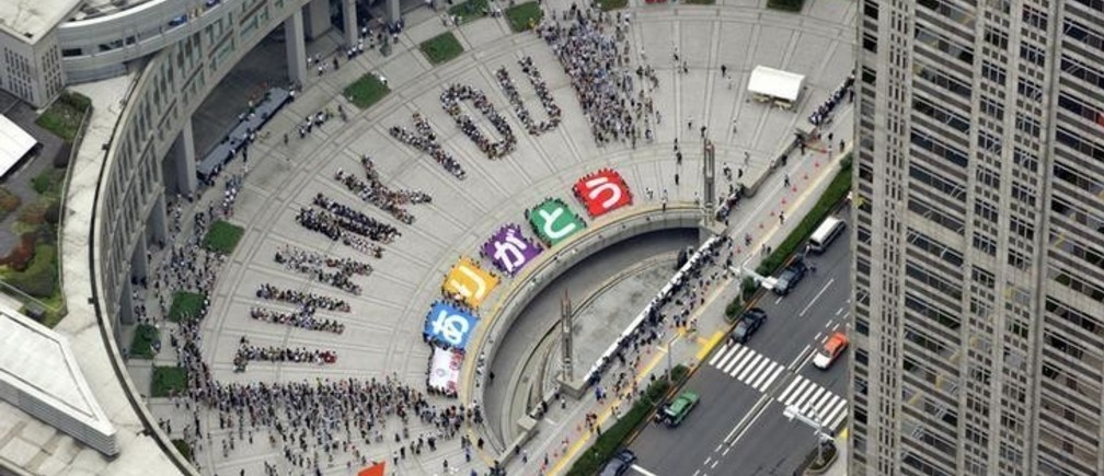"An aerial view shows people sitting in formation to the words ""thank you"" and displaying signs that collectively read ""Arigato"" (Thank You) during an event celebrating Tokyo being chosen to host the 2020 Olympic Games, at Tokyo Metropolitan Government Building in Tokyo, in this photo taken by Kyodo September 8, 2013. Tokyo was awarded the 2020 summer Olympic Games on Saturday, beating Istanbul in a head-to-head vote after Japanese Prime Minister Shinzo Abe delivered a charismatic plea to the International Olympic Committee and promised Japan's crippled nuclear plant was ""under control."" MANDATORY CREDIT.  REUTERS/Kyodo (JAPAN - Tags: POLITICS SPORT OLYMPICS TPX IMAGES OF THE DAY) ATTENTION EDITORS - THIS IMAGE HAS BEEN SUPPLIED BY A THIRD PARTY. IT IS DISTRIBUTED, EXACTLY AS RECEIVED BY REUTERS, AS A SERVICE TO CLIENTS. FOR EDITORIAL USE ONLY. NOT FOR SALE FOR MARKETING OR ADVERTISING CAMPAIGNS. MANDATORY CREDIT. JAPAN OUT. NO COMMERCIAL OR EDITORIAL SALES IN JAPAN"
