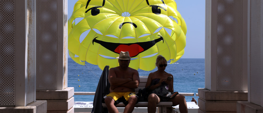 People sit on a bench on the Promenade des Anglais in front of a happy face design on a parascending during a sunny summer day in Nice, France, July 10, 2019.     REUTERS/Eric Gaillard - RC15EC1AAE00