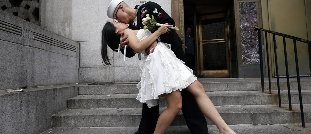 U.S. Navy Petty Officer 3rd Class EO3 John Chen, 23, from Lakehurst, New Jersey, kisses his new bride Victoria Chan, 25,December 12, 2012.  REUTERS/Mike Segar