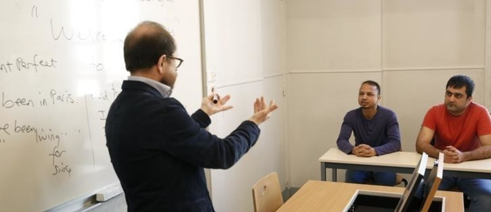 Teacher George Ferenci (L) speaks to asylum seekers Minawar Ahmadzai from Afghanistan (R) and Mohammed Salah Uddin Ahmed from Bangladesh (C) during an English class for refugees at Paris' Sciences Po university in Paris, France, March 15, 2016. REUTERS/Philippe Wojazer      TPX IMAGES OF THE DAY
