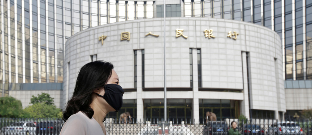 A woman walks past the headquarters of the People's Bank of China (PBOC), the central bank, in Beijing, China September 28, 2018
