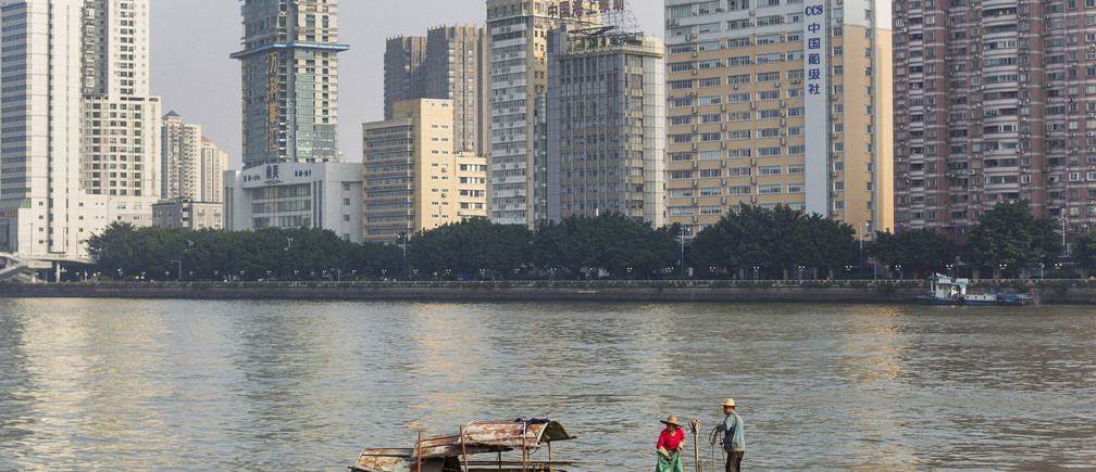 A couple fishing along Pearl River (or Zhu Jiang) next to office buildings in downtown Guangzhou, Guangdong province December 7, 2013. The Pearl River is China's second largest river by volume after the Yangtze River. Fisherman on the River are lately faced with periodic banning of fishing by Chinese government in an effort to protect the area's fishery resources, according to local media. Picture taken December 7, 2013. REUTERS/Stringer (CHINA - Tags: SOCIETY AGRICULTURE CITYSCAPE) - RTX169CP