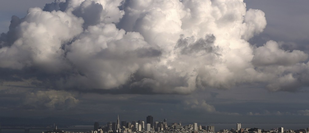 A large cloud gathers over the skyline of San Francisco, California December 12, 2014. A major storm pummeled California and the Pacific Northwest with heavy rain and high winds on Thursday, killing one man, knocking out power to tens of thousands of homes, disrupting flights and prompting schools to close. REUTERS/Robert Galbraith (UNITED STATES - Tags: ENVIRONMENT CITYSCAPE TPX IMAGES OF THE DAY) - RTR4HU40
