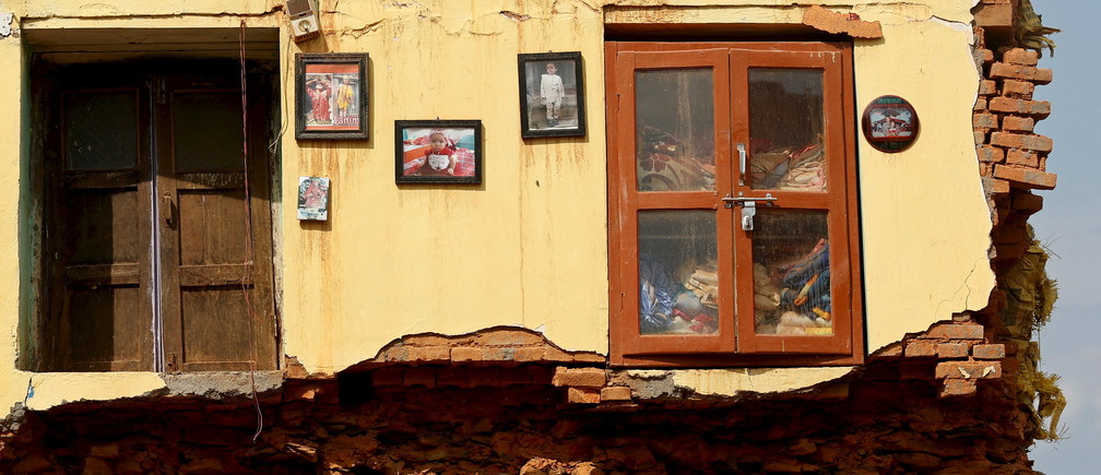 Framed pictures are seen hanging from the wall of a house damaged by earthquakes in Sindhupalchowk district, Nepal, May 13, 2015. REUTERS/Ahmad Masood      TPX IMAGES OF THE DAY      - GF10000093335