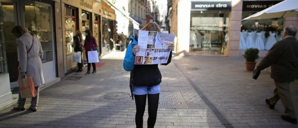 A woman covers her face with a city map in reaction to the photographer, in the central Andalusian capital of Seville January 3, 2013.  REUTERS/Marcelo del Pozo (SPAIN - Tags: SOCIETY TRAVEL)