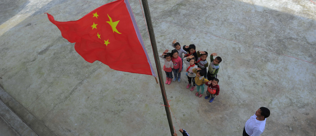 Pupils salute as they participate in a flag-raising ceremony with their teacher at a primary school in Longli county, Guizhou Province, China, May 31, 2016. REUTERS/Stringer ATTENTION EDITORS - THIS IMAGE WAS PROVIDED BY A THIRD PARTY. EDITORIAL USE ONLY. CHINA OUT. NO COMMERCIAL OR EDITORIAL SALES IN CHINA.       - RTX2F9OU