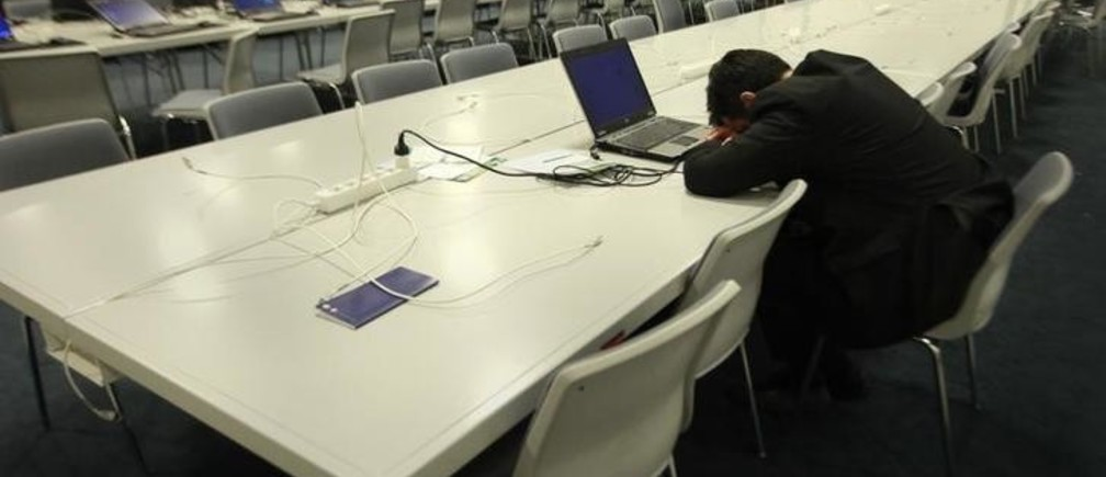 A delegate sleeps in the Bella Center as negotiators worked through the night to form a draft text at the UN Climate Change Conference 2009 in Copenhagen December 18, 2009. REUTERS/Bob Strong  (DENMARK - Tags: ENVIRONMENT)