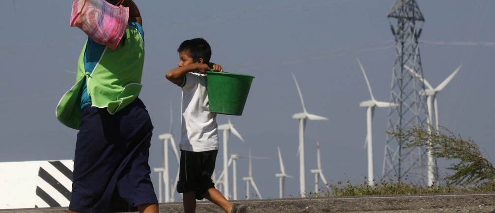 A woman and a boy walk past wind turbines and an electricity tower in La Ventosa February 7, 2012.