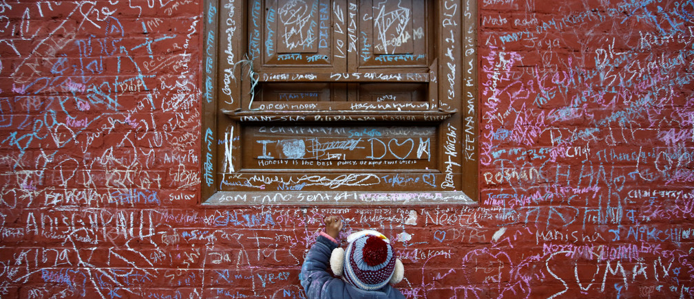 A child writes with chalk on a wall to celebrate Shreepanchami festival at Saraswati temple in Kathmandu, Nepal February 1, 2017. Children are given their first writing and reading lessons at the temple during this festival in the belief that the goddess of education Saraswati will help them excel in education. REUTERS/Navesh Chitrakar     TPX IMAGES OF THE DAY - RC197B507EC0