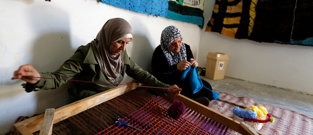 A Syrian woman weaves wool as a colleague knits a baby shawl at a shelter for women built by the Italian NGO Building Peace Foundation and run by UN Women at Al Zaatari refugee camp outside Mafraq, Jordan.