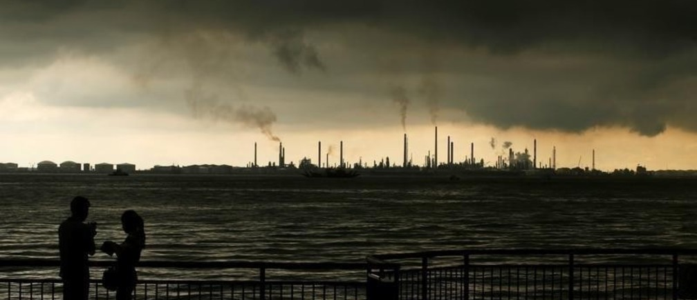 Storm clouds gather over Shell's Pulau Bukom oil refinery in Singapore December 17, 2014.