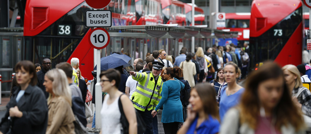 A police officer directs a woman as commuters wait for buses at Victoria Station in London, Britain August 6, 2015.  REUTERS/Darren Staples