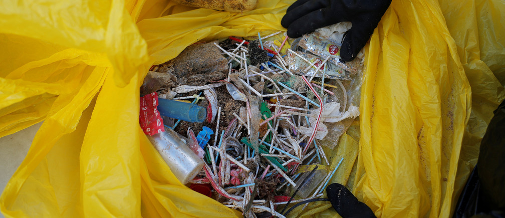 A volunteer shows ear sticks and plastics after a garbage collection, ahead of World Environment Day on La Costilla Beach, on the coast of the Atlantic Ocean in Rota, Spain June 2, 2018. REUTERS/Jon Nazca - RC193FA08000