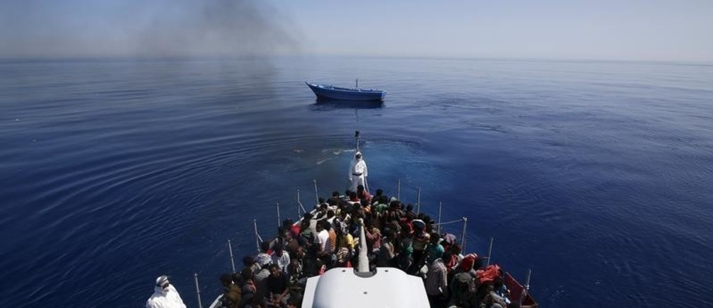 A group of 300 sub-Saharan Africans (bottom) sit on board the Italian Finance Police vessel Di Bartolo as their boat (Top) is left to adrift off the coast of Sicily, May 14, 2015. Around 1100 migrants were rescued off the coast of Sicily, about 130 miles from Lampedusa, according to the police.REUTERS/Alessandro Bianchi