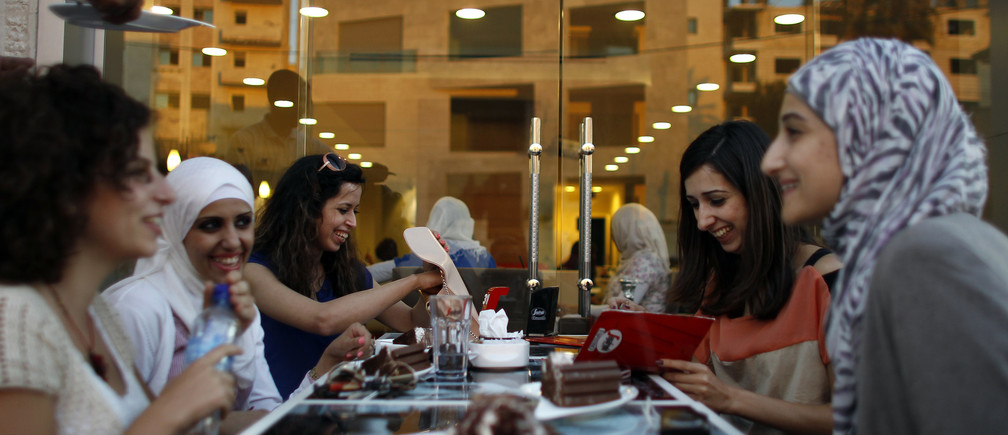 Palestinian women sit together at a newly opened upscale Italian cafe in the West Bank city of Ramallah July 3, 2012.