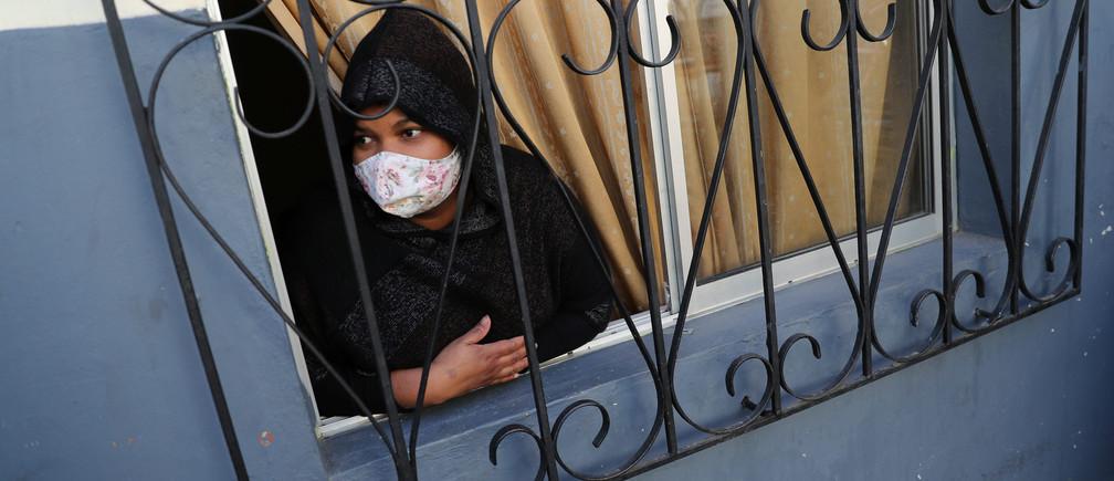 Un inmigrante peruano mira desde su ventana a un barrio pobre, durante una cuarentena general en medio de la propagación de la enfermedad coronavirus (COVID-19) en Santiago de Chile el 22 de mayo de 2020.