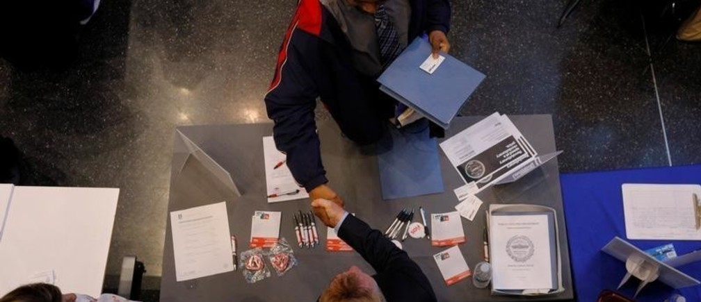 Job seeker Tony Harris (top) shakes hands with a representative from Verizon at a City of Boston Neighborhood Career Fair in Boston, Massachusetts, U.S., May 1, 2017.   REUTERS/Brian Snyder - RC14442C6AE0