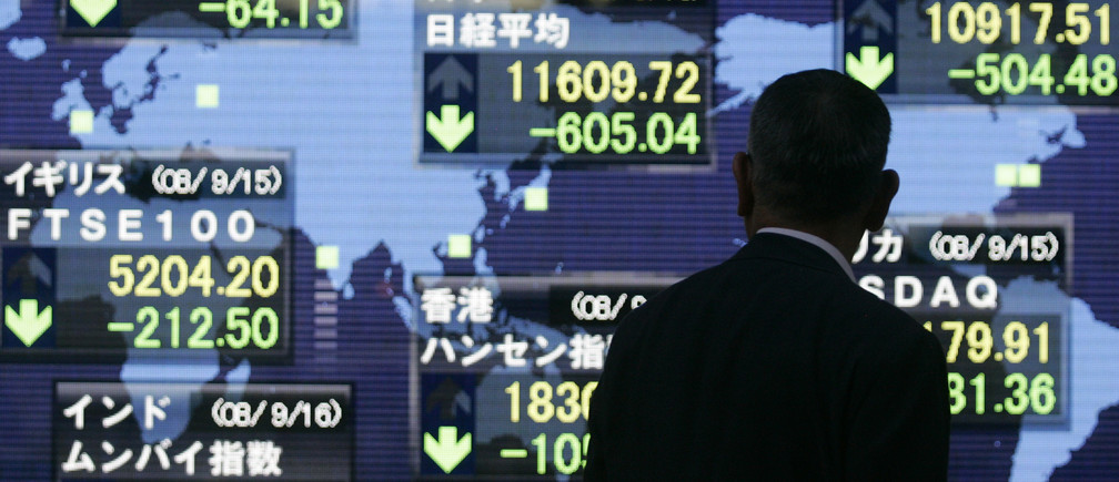 A businessman looks at an electronic board displaying falls in major indices in Tokyo September 16, 2008. The benchmark Nikkei average slid 5 percent to a three-year low on Tuesday, with investors dumping share across the board after Lehman Brothers' collapse fuelled fears about the U.S. financial system and hit stock markets worldwide
