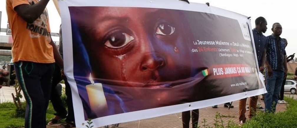 People carry a banner during a remembrance ceremony for the children who were killed during an attack on the Dogon village of Sobane Da, at the Monument de la Paix in Bamako, Mali June 15, 2019. REUTERS/Annie Risemberg - RC1979B34AA0