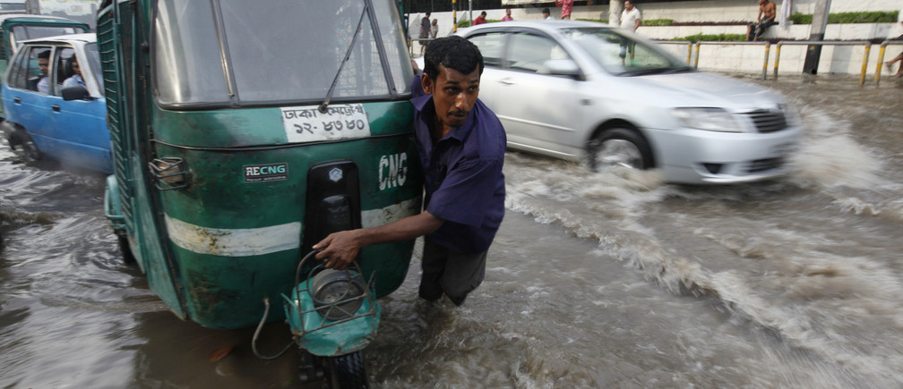 A driver pulls his broken down vehicle in knee deep water caused by heavy rainfall in Dhaka, 2010.