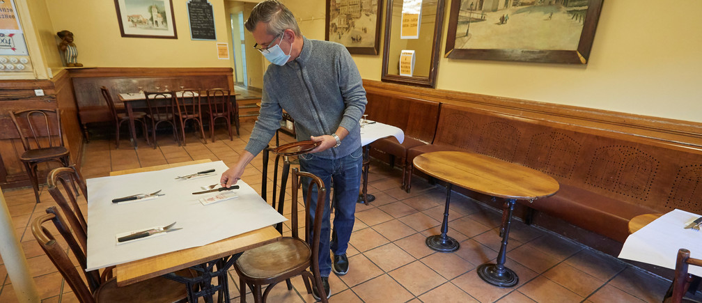 Gerald Bongioanni sets a table on the reopening day of the Cafe du Soleil as Switzerland eases the lockdown measures during the coronavirus disease (COVID-19) outbreak in Geneva, May 11, 2020. REUTERS/Denis Balibouse - RC2AMG9GO0J0