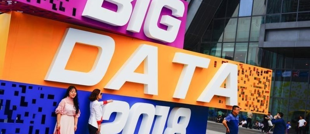 People have their picture taken by the China International Big Data Industry Expo logo in Guiyang, Guizhou province, China May 26, 2018. Picture taken May 26, 2018.  REUTERS/Stringer ATTENTION EDITORS - THIS IMAGE WAS PROVIDED BY A THIRD PARTY. CHINA OUT. - RC1A01CDD6E0